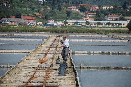 crystallization:  Seca, Slovenia, 04.15.09: A man works in a salt flats crystallization field near Seca Editorial