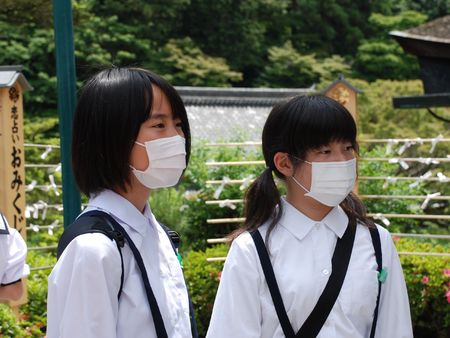 Kyoto, Japan, 23.5.09: Two Japanese school girls on an outing to a temple in Kyoto wear facemasks like most of their classmates during the Swine Flu scare Editorial