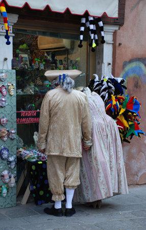 vestidos de epoca: Venecia, Italia, 02.21.09: Una pareja en pleno per�odo de vestuario navegar en una tienda de recuerdos durante el Carnaval de Venecia anual  Editorial