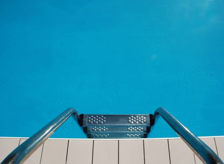 Steps lead down into the clear blue waters of a well kept swimming pool