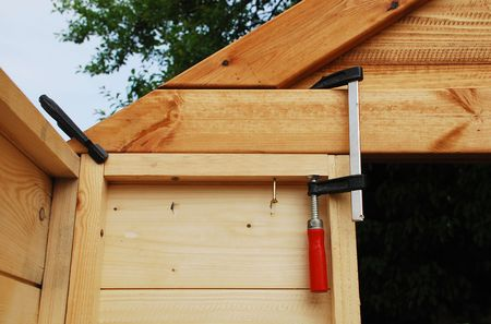 positioned: Two red handled wood working clamps holding together a wall panel and a roof end of a wooden prefabricated garden shed which is under construction