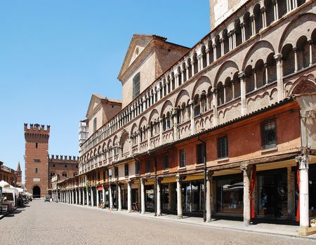 The historic Piazza Trento e Trieste in Ferrara, Emilia-Romagna, Italy. These medieval buildings are located at the side of the cathedral, and the City Hall can be seen in the photograph at the end of the street. Stock Photo