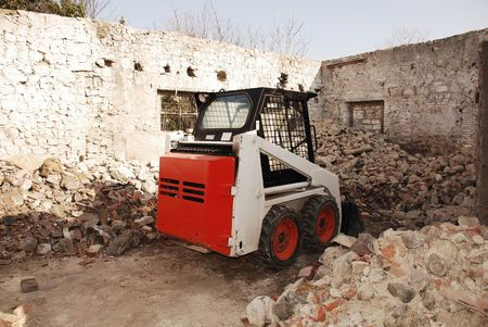 bulldoze: A skid steer loader in a partially demolished derelict old Italian farm building