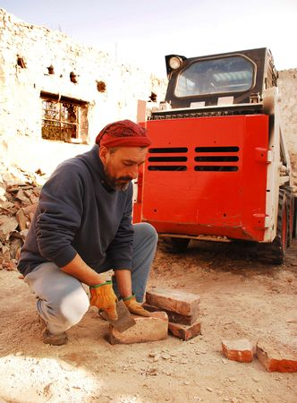 A man scrapes excess cement from antique bricks being salvaged for further architectural use from the demolition site of an old Italian farm building photo