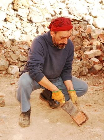 A man scrapes excess cement from antique bricks being salvaged for further architectural use from the demolition site of an old Italian farm building Stock Photo - 8361748