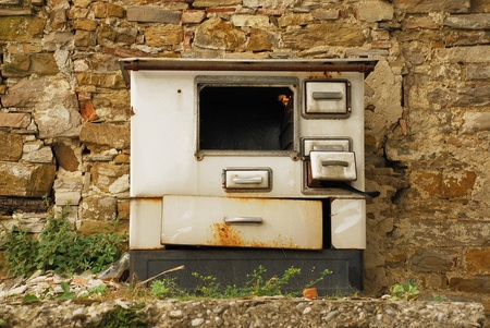 An old abandoned wood burning cooker, left in a street in Smartno, Slovenia Stock Photo