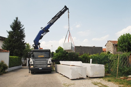 A truck with a telescopic crane delivers packages containing a wood (fir) block house, a pre-cut wooden house which is assembled on-site  Stock Photo