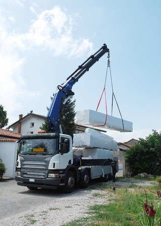 A truck with a telescopic crane delivers packages containing a wood (fir) block house, a pre-cut wooden house which is assembled on-site photo
