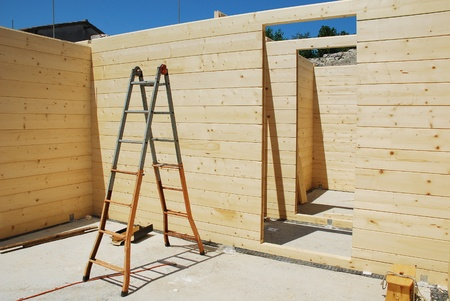 A ladder and empty door frames in a partially constructed wood (fir) block house, a pre-cut wooden house which is assembled on-site