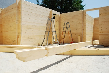 Ladders in a partially constructed wood (fir) block house, a pre-cut wooden house which is assembled on-site. Some of the roof beams are on the floor in the foreground Stock Photo