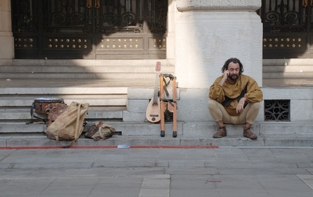 Udine, Italy -  September 17th 2011 - A street musician dressed in medieval costume takes a rest from performing and chats on his mobile phone during the 2011 annual Friuli Doc (Udine) celebration of locally produced food, drinks and crafts  (Friuli Doc)