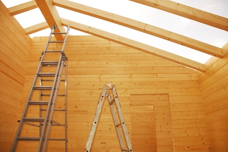 Ladders and empty door frames in a partially constructed wood (fir) block house, a pre-cut wooden house which is assembled on-site