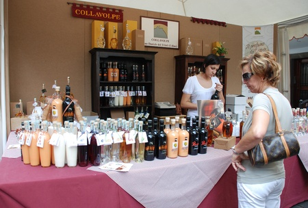 Udine, Italy -  September 17th 2011 -  A selection of locally produced alcoholic drinks on display at a street stall during  Friuli Doc . The potential customer is being served a free sample Stock Photo - 10977394