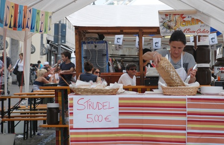 Udine, Italy, September 17th 2011. A woman fills a serving basket with freshly made strudels on a strudel stall during the 2011 annual Friuli Doc celebration of locally produced food, drinks and crafts