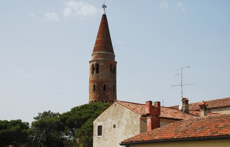 11th century: The 11th century belltower in Caorle, in the Veneto region of Italy, with historic foreground buildings. Stock Photo