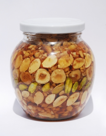 A jar of Greek honey and nuts  pistachios, peanuts, hazelnuts, pine nuts, almonds, walnuts  in natural light