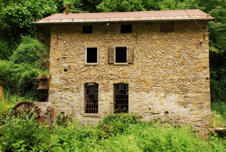 watermills: An old abandoned mill near Salino in Friuli, north east Italy  It has a water wheel mounted vertically on a horizontal axis  Stock Photo