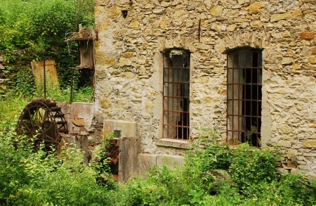 watermills: The water wheel  mounted vertically on a horizontal axis  and windows of an old abandoned mill near Salino in Friuli, north east Italy