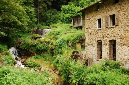 watermills: An old abandoned mill near Salino in Friuli; north east Italy  It has a water wheel mounted vertically on a horizontal axis