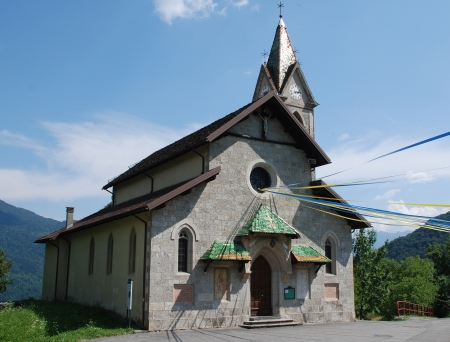The church of Chiesa di San Antonio in the Italian village of Mione in Friuli. The church has bunting outside of it in celebration of the village annual summer fete photo
