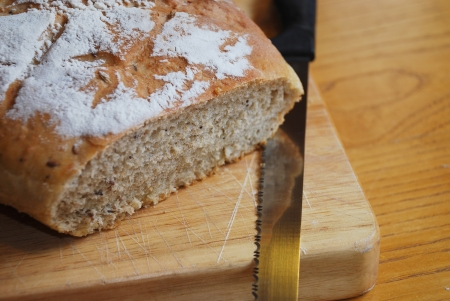 A loaf of home-baked sourdough bread on a wooden chopping board on a wooden table with a large black-handled knife in natural lighting photo