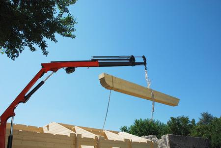prefabricated buildings: La viga principal se baje a su posici�n en una madera de abeto casa de bloque prefabricado parcialmente construido en un solar dom�stica Foto de archivo