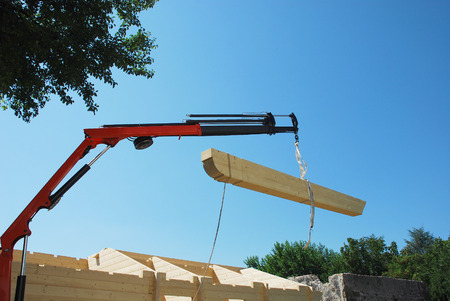 The main beam being lowered into position on a partially constructed wood  fir  prefabricated block house on a domestic building site