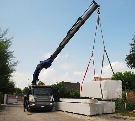 テレスコ ピック クレーン付きトラックがモミの木ブロックの家、敷地内に組み立てられるプレカット木造住宅を含むパッケージを提供します。