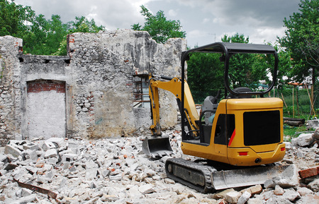 A compact excavator on a small domestic building site where a breezeblock building has just been demolished  The remains of an old Italian stone farmbuilding can be seen in the background