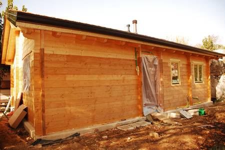 A newly constructed but incomplete wooden  fir  prefabricated house with rain guttering and fitted windows