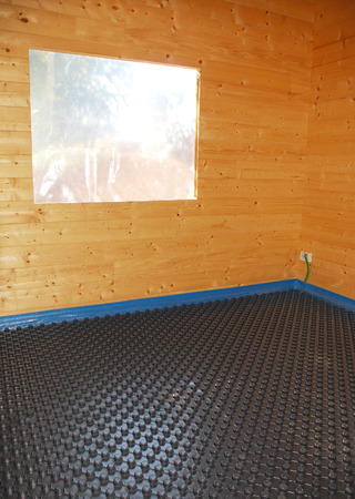 A room in a partially constructed wooden house with black plastic molded insulated panel  photo