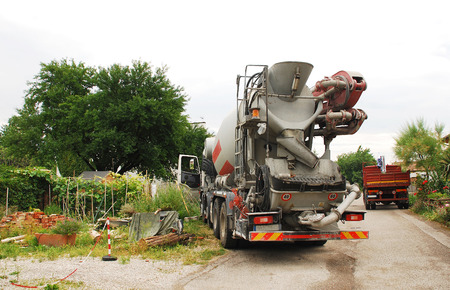 onsite: A concrete mixer truck delivering concrete to a small domestic building site in north east Italy  Such vehicles use a revolving drum to mix the ingredients and are able to supply ready-mixed concrete on site