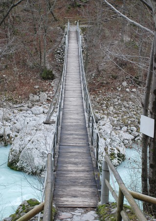 neighbouring: A wood and rope suspension bridge in Slovenia over the Soca River  known as the Isonzo in neighbouring Italy
