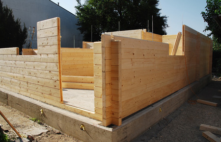 prefab: A partially constructed wood  fir  prefabricated block house on a domestic building site  The front door can in the foreground  Stock Photo