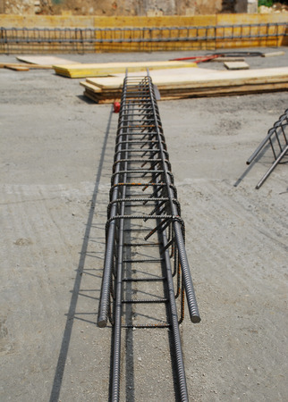 Steel reinforcement cage used in the construction of building foundations  The foundation site is surrounded by wooden shuttering and the steel cages are in the process of being laid out before the concrete is poured photo
