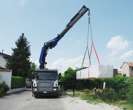 prefab: A truck with a telescopic crane delivers packages containing a wood  fir  block house, a pre-cut wooden house which is assembled on-site Stock Photo