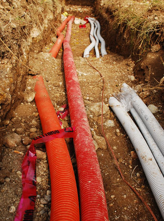 A utilities trench at the side of a newly build wood  fir  house  The trench carries the conduits for gas, water, electric, sewage and phone services