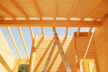 Roof construction on a partially constructed wood  fir  block house, a pre-cut wooden house which is assembled on-site Stock Photo