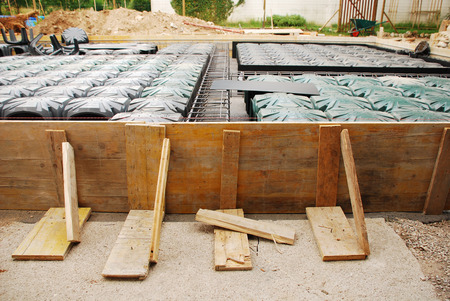 radon: A house foundation site with steel reinforcement cages and radon iglus surrounded by wooden shuttering  The cages and iglus have been laid out ready for the concrete to be poured  Stock Photo
