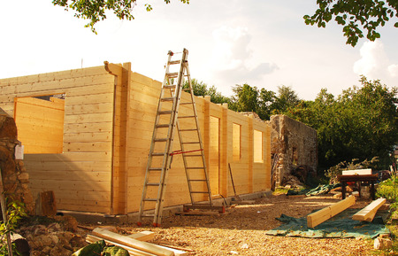 prefabricated: A partially constructed wood  fir  prefabricated block house on a domestic building site  This is a view of the back of the house  An old stone farmhouse can be seen in the background