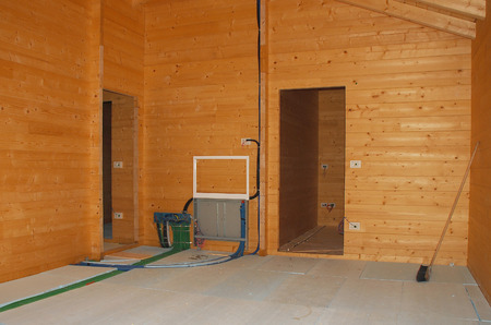 manifold: The interior of a partially completed new wooden  fir  prefabricated blockhouse  Floor insulation has been laid on top of an underfloor central heating system ahead of a top layer of concrete  The hot water and central heating manifold can be seen on the  Stock Photo