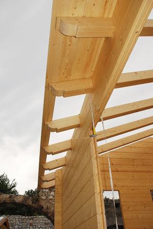 prefabricated buildings: La construcci�n del techo en una casa de bloque abeto madera construida en parte, una casa de madera pre-cortadas que se monta en el lugar Foto de archivo