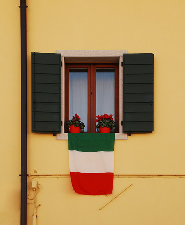 An Italian flag - Il Tricolore - hangs out of the window of an old rural village building photo