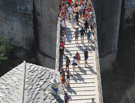 Mostar, Bosnia and Herzegovina - August 13th 2014. Tourists stroll across the Old Bridge (Stari Most) in Mostar during peak tourist season