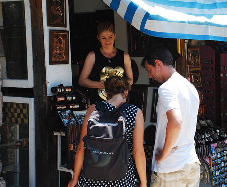 tourists stop: Mostar, Bosnia and Herzegovina - August 13th 2014. Tourists stop outside a souvenir shop near Stari Most (the Old Bridge) to look at the goods for sale in Mostar during peak tourist season