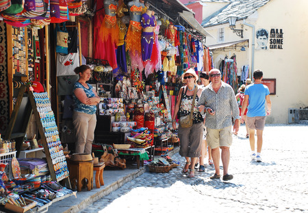 tat: Mostar, Bosnia and Herzegovina - August 13th 2014. Tourists stroll past a souvenir shop near Stari Most (the Old Bridge) to look at the goods for sale in Mostar during peak tourist season