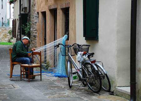 Grado, Italy - September 12th 2014. An old fisherman mends nets outside of his home in the beach town of Grado