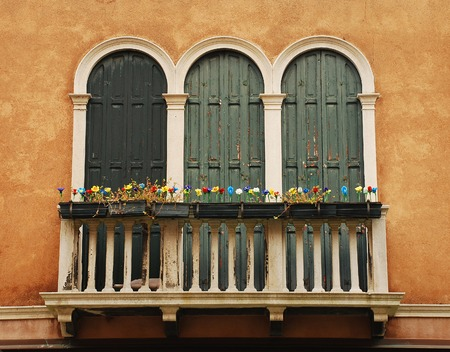 glasswork: A small balcony in a wall in an historic building in Muano, Venice, Italy. Murano is famous for its glasswork - the flowers on the balcony are made of locally produced glass Editorial