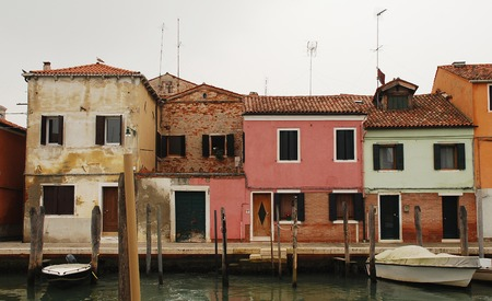 tatty: Boats outside historic waterfront buildings on the Venice island of Murano, Italy, on a cold autumn day