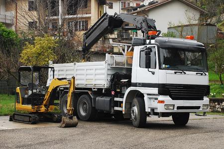 camion grua: Un mini excavadora hidráulica compacta con una plataforma giratoria casa y un basculante de gruas.
